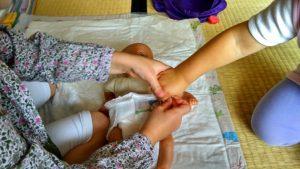 Eine helfende Hand beim erlernen des Wickelns